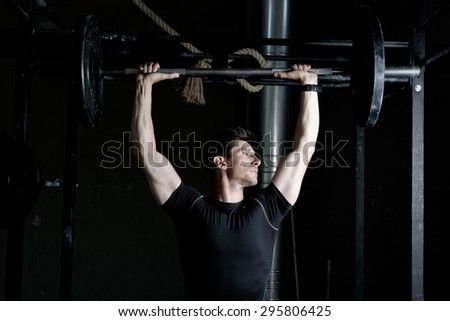 Athlete Fitness trainer working out / weight lifting in a gym - stock photo
