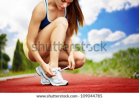 Athlete girl trying running shoes getting ready for jogging - stock photo