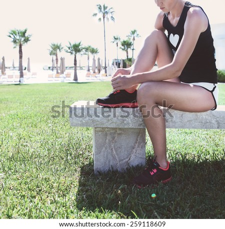 Athlete girl trying running shoes getting ready for jogging in the park. Toned image - stock photo