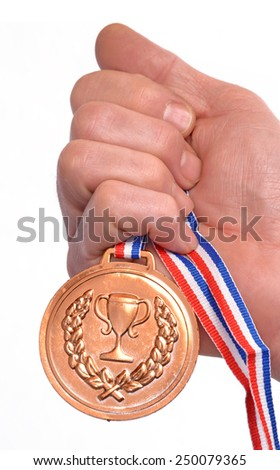 Athlete hand holding gold medal.Award winner hand holding a gold medal isolated on white background. - stock photo