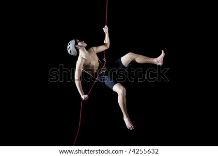 Athlete hanging on rope-hiking-isolated on black background - stock photo