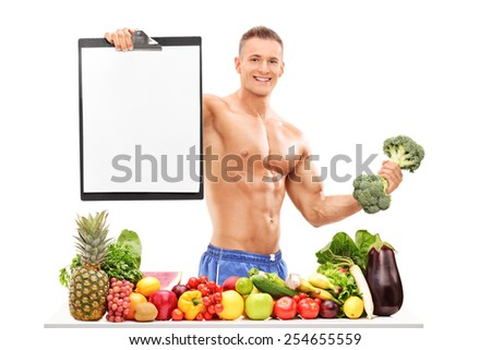 Athlete holding a broccoli dumbbell and a clipboard behind a pile of vegetables isolated on white background - stock photo