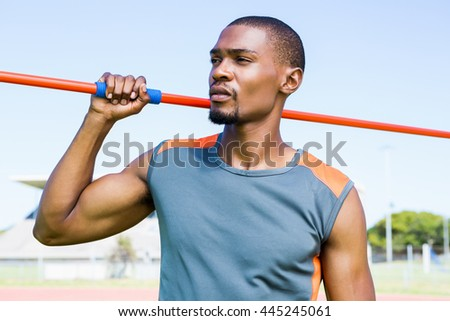 Athlete holding javelin in stadium on a sunny day