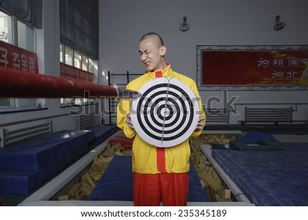 Athlete Holding Target as Javelin Approaches - stock photo
