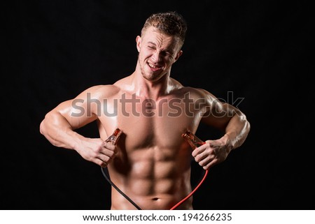 athlete holds the high voltage wires. beats his current