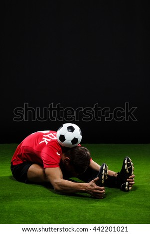 Athlete in black and red uniform doing warming exercise with soccer ball on  grass over black background - stock photo