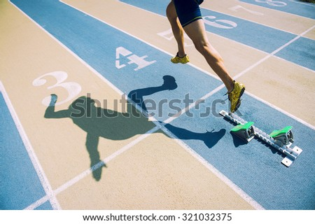 Athlete in gold shoes sprinting from the starting blocks over the starting line of a race on a blue and tan running track  - stock photo