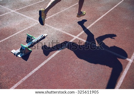 Athlete in gold shoes sprinting from the starting blocks over the starting line of a race on a red running track  - stock photo