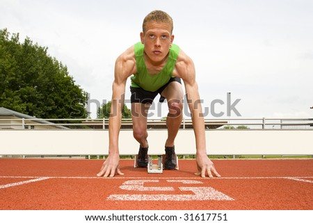 Athlete in lane five, set to start in the starting blocks for a sprint run - stock photo
