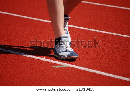 Athlete in running shoes warming up on the racetrack