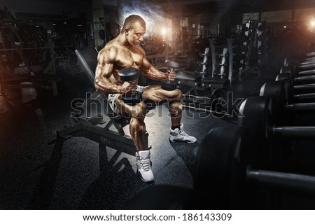 Athlete in the gym training with dumbbells - stock photo