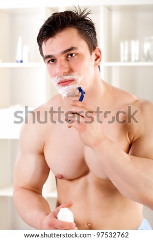 athlete is a young guy shaves in the bathroom - stock photo