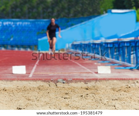 athlete jumps in length, sports background - stock photo