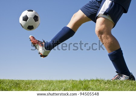 Athlete Kicking a soccer ball on field - stock photo