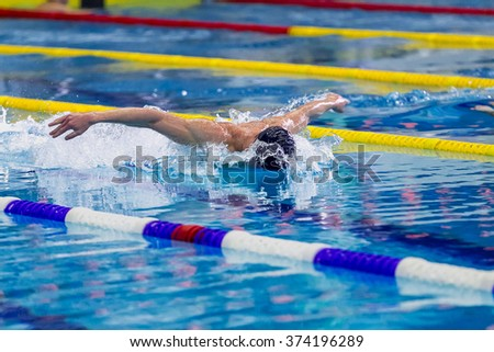 athlete male swimmer swimming in pool butterfly. side view - stock photo