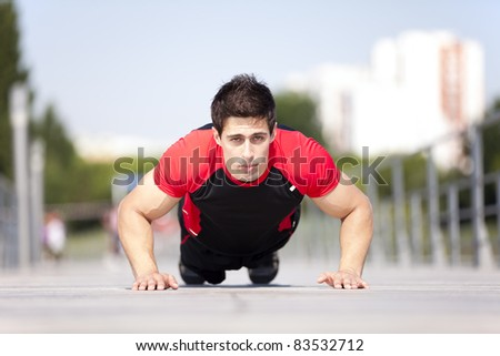 Athlete man at the city park making some pushup - stock photo