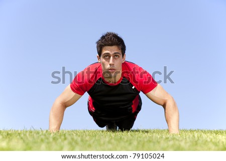 Athlete man at the park making some push up - stock photo