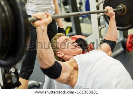 Athlete man does bench press exercise in gym hall under supervision of female coach