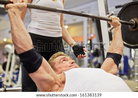 Athlete man does bench press from chest exercise in gym hall under supervision of female coach - stock photo