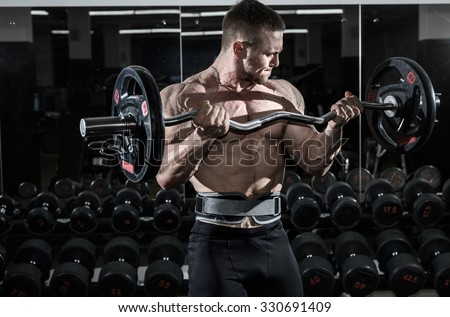 Athlete muscular bodybuilder in the gym training biceps with bar. - stock photo