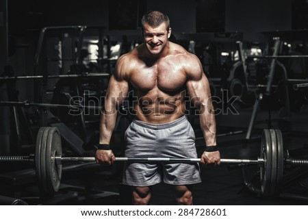 Athlete muscular bodybuilder in the gym training dead lift with barbell - stock photo