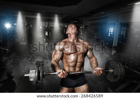 Athlete muscular bodybuilder in the gym training with bar - stock photo