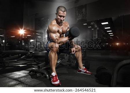 Athlete muscular bodybuilder in the gym training with dumbbells - stock photo