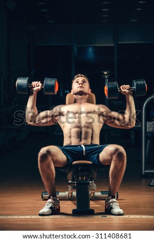 Athlete muscular bodybuilder training back with dumbbell  in the gym. - stock photo