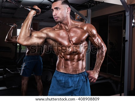 Athlete muscular bodybuilder training on simulator in the gym