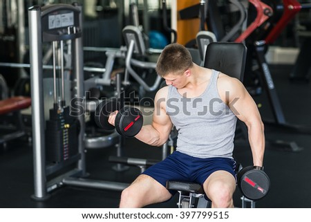 Athlete muscular bodybuilder training with dumbbell  in the gym.  - stock photo