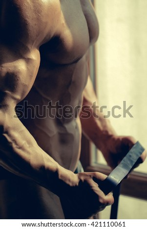 Athlete muscular bodybuilder with torso side chest six pack abdominal muscles biceps triceps train with resistance band in gym on light background  - stock photo