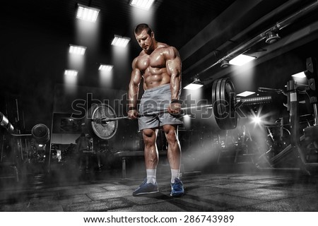 Athlete muscular brutal bodybuilder training workout with heavy barbell in the gym - stock photo