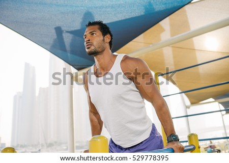 Athlete muscular fitness male model pulling up on horizontal bar in a park outdoor
