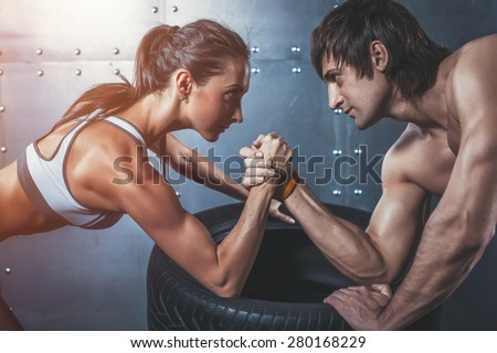 Athlete muscular sportsmen man and woman with hands clasped arm wrestling challenge between a young couple Crossfit fitness sport training lifestyle bodybuilding concept - stock photo