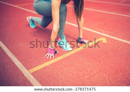 athlete on starting blocks at stadium track preparing for a sprint. Fitness, healthy lifestyle concept - stock photo