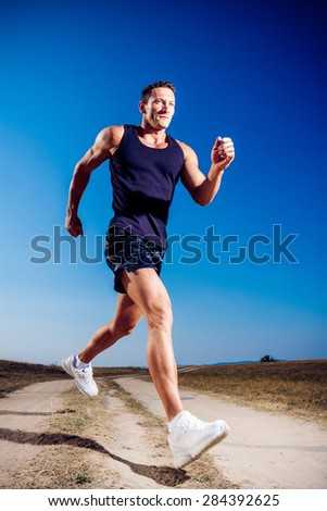 Athlete outside in nature on a dusty road - stock photo