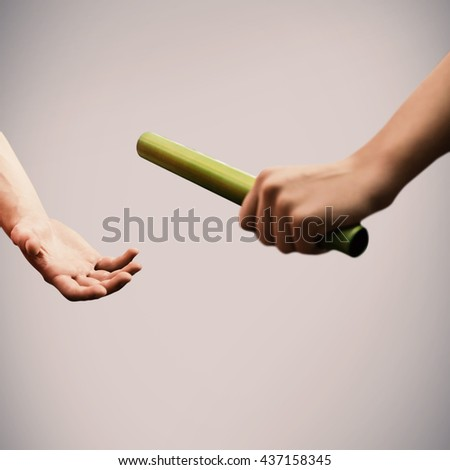 Athlete passing a baton to the partner - stock photo