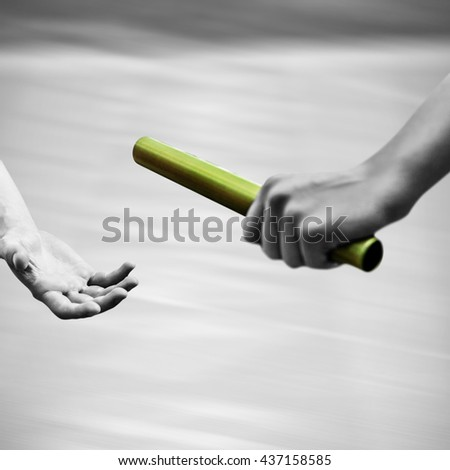 Athlete passing a baton to the partner with colored baton - stock photo