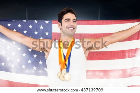Athlete posing with gold medals and american flag after victory on a black background - stock photo