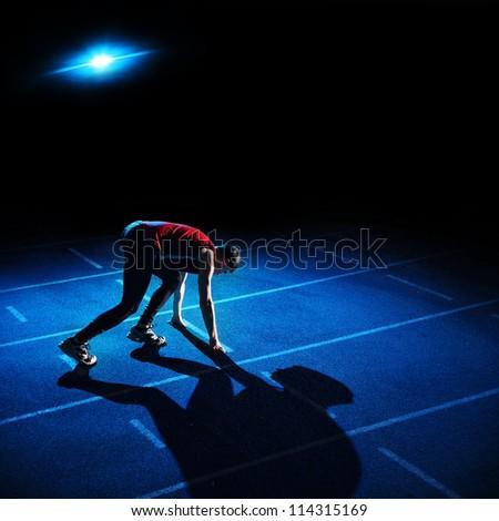 Athlete preparing to start on blue running track - stock photo