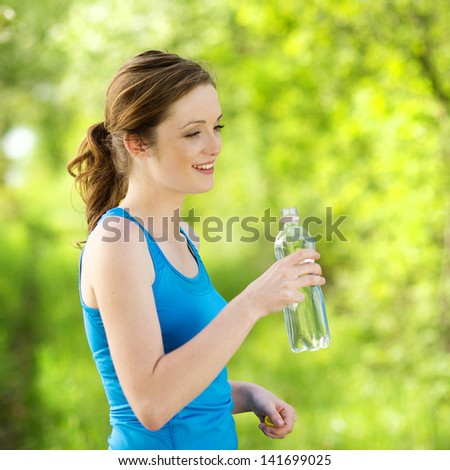 Athlete refreshing with a bottle of water during the outdoor exercise - stock photo
