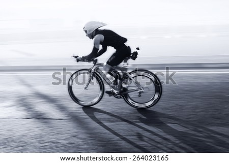 Athlete riding bicycle at sunny day on coastal road, blurred motion - stock photo