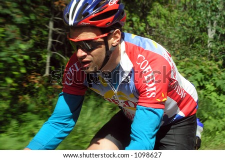 Athlete riding bicycle with motion background - stock photo