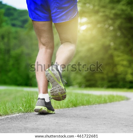 Athlete runner feet running on road closeup on shoe. Man fitness sunrise jog workout wellness concept.