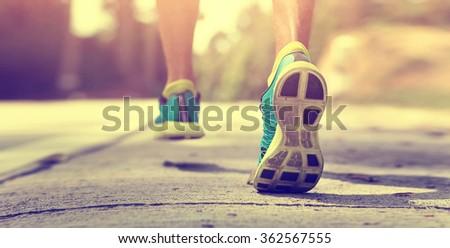 Athlete runner feet running on treadmill closeup on shoe - stock photo