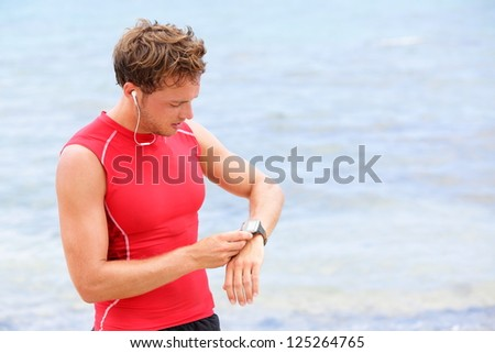 Athlete runner looking at heart rate monitor watch. Man running on beach taking a break in compression t-shirt top. - stock photo