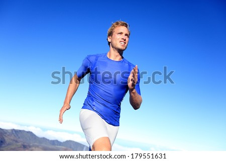 Athlete runner sprinting running to success. Fit male fitness sprinter training in sprint with determination and strength. Handsome athletic man working out outside on blue sky. - stock photo
