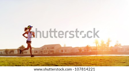 Athlete running at sunset panorama with copyspace - stock photo