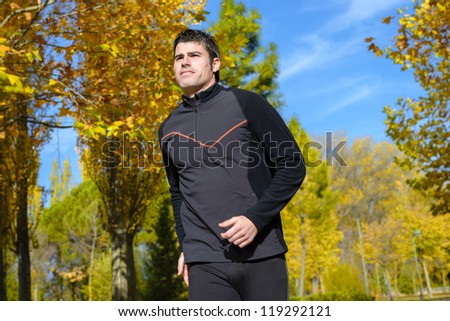 Athlete running on autumn park. Athlete exercising outdoors with trees on background. - stock photo