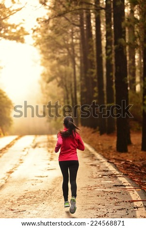 Athlete running on road in morning sunrise training for marathon and fitness. Healthy active lifestyle woman exercising outdoors. - stock photo
